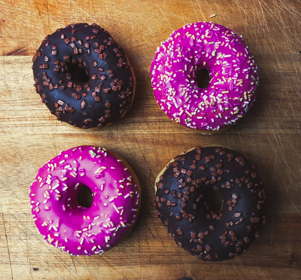 two chocolate donuts and two pink donuts