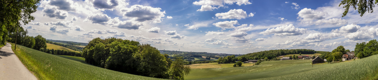 Super Panorama of a Beautiful rural landscape in Germany with blue sky, impressive clouds and a wonderful little farm
