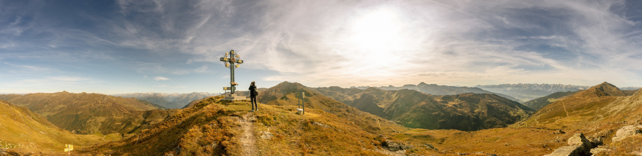 Landscape panorama of the Austrian Alps Hiker stands at the summit cross