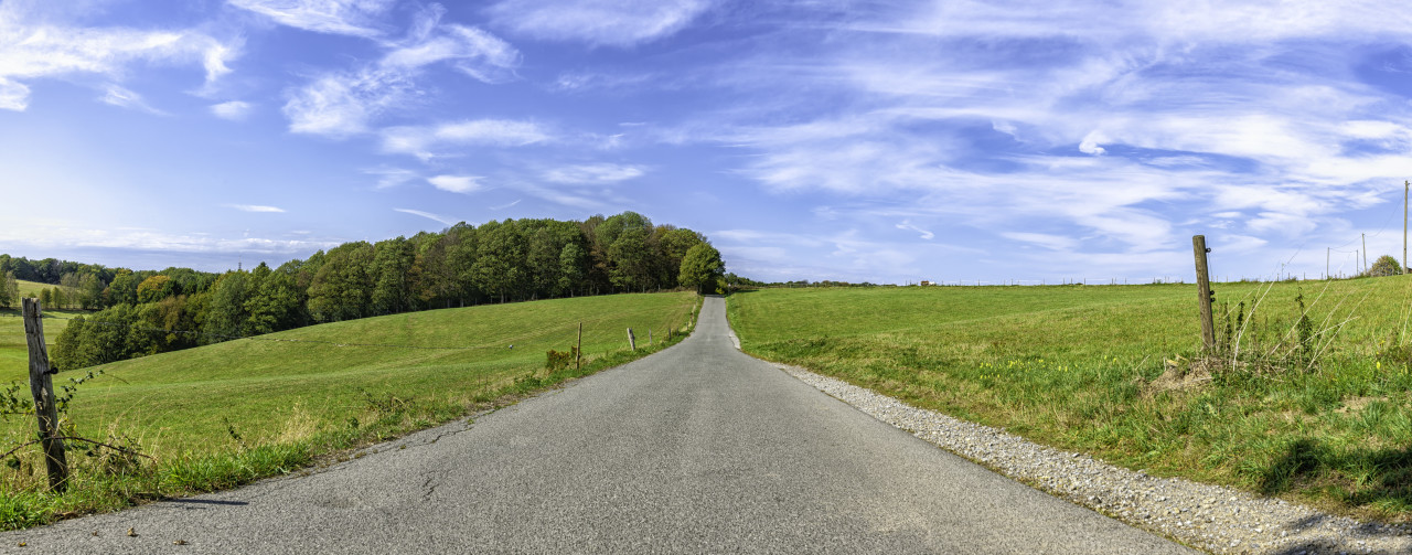 country road through rural landscape with field and blue sky, wuppertal ronsdorf, nrw germany
