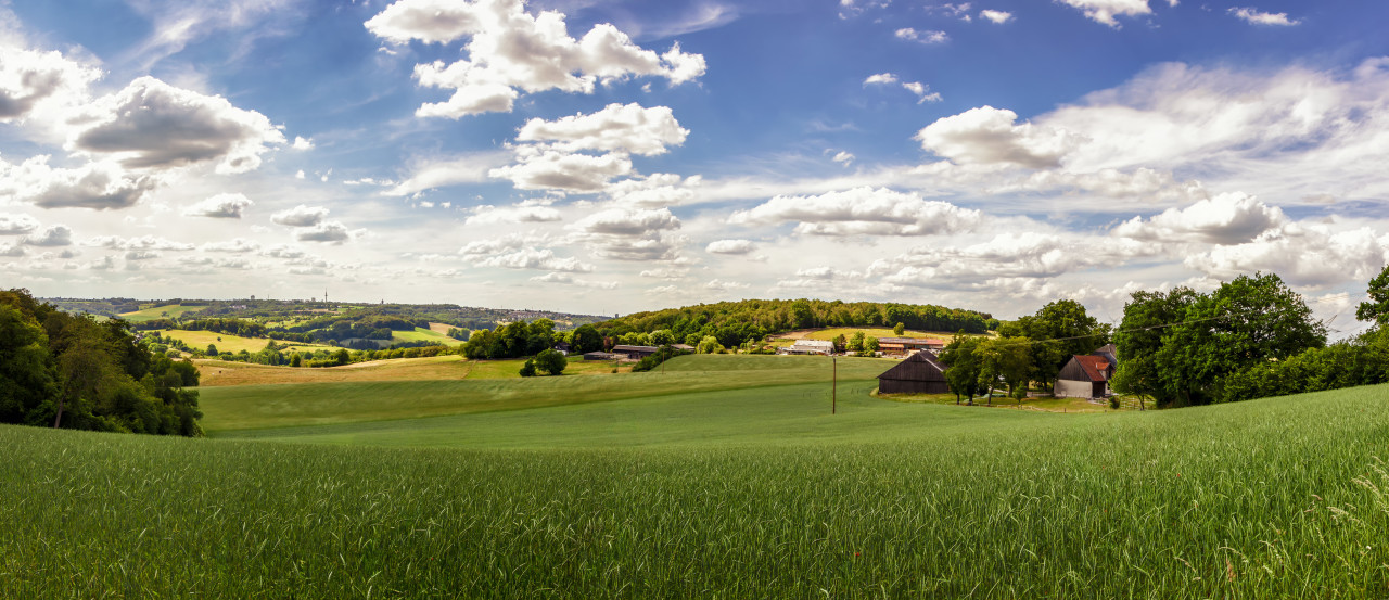 Beautiful rural landscape panorama in Germany with blue sky, impressive clouds and a wonderful little farm