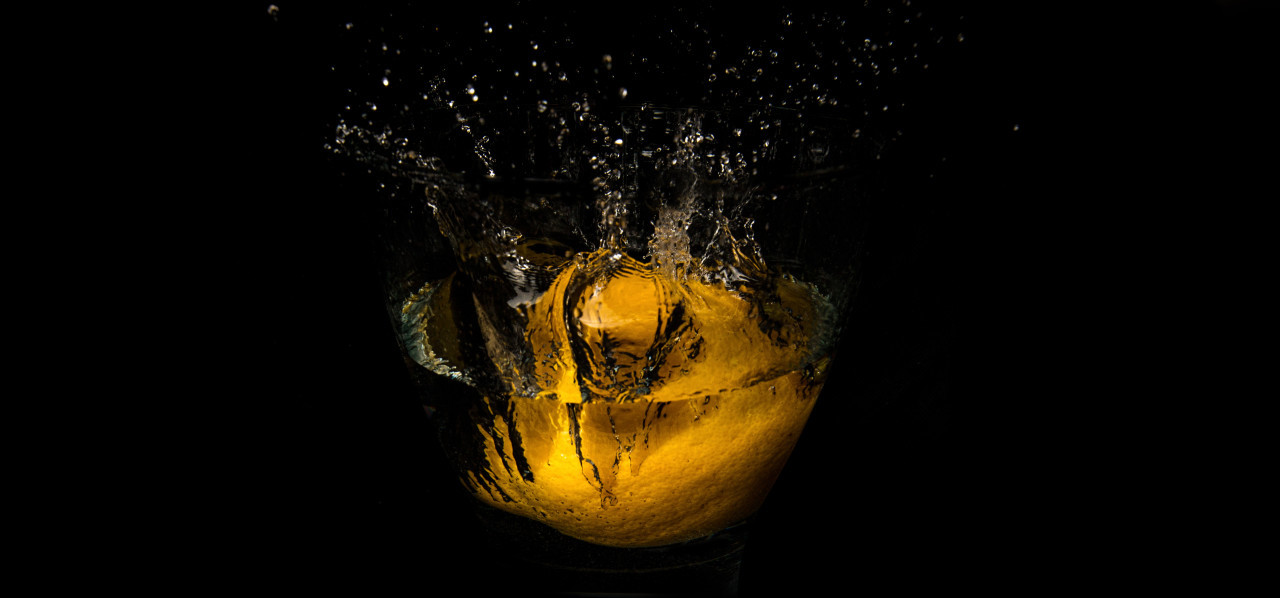 lemon falls into the water isolated on black background