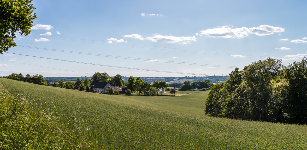 German rural landscape near Velbert Langenberg with fields and hills and a Farm in Background