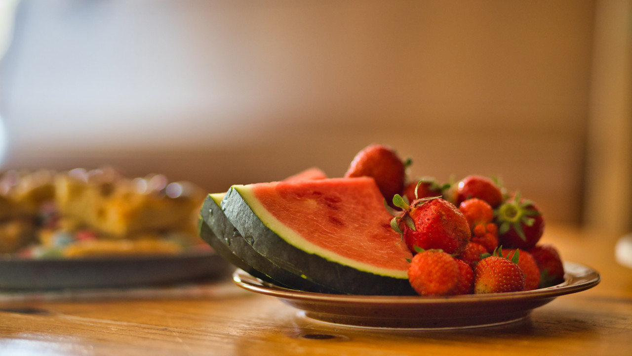 A plate of watermelon slices and fresh strawberries