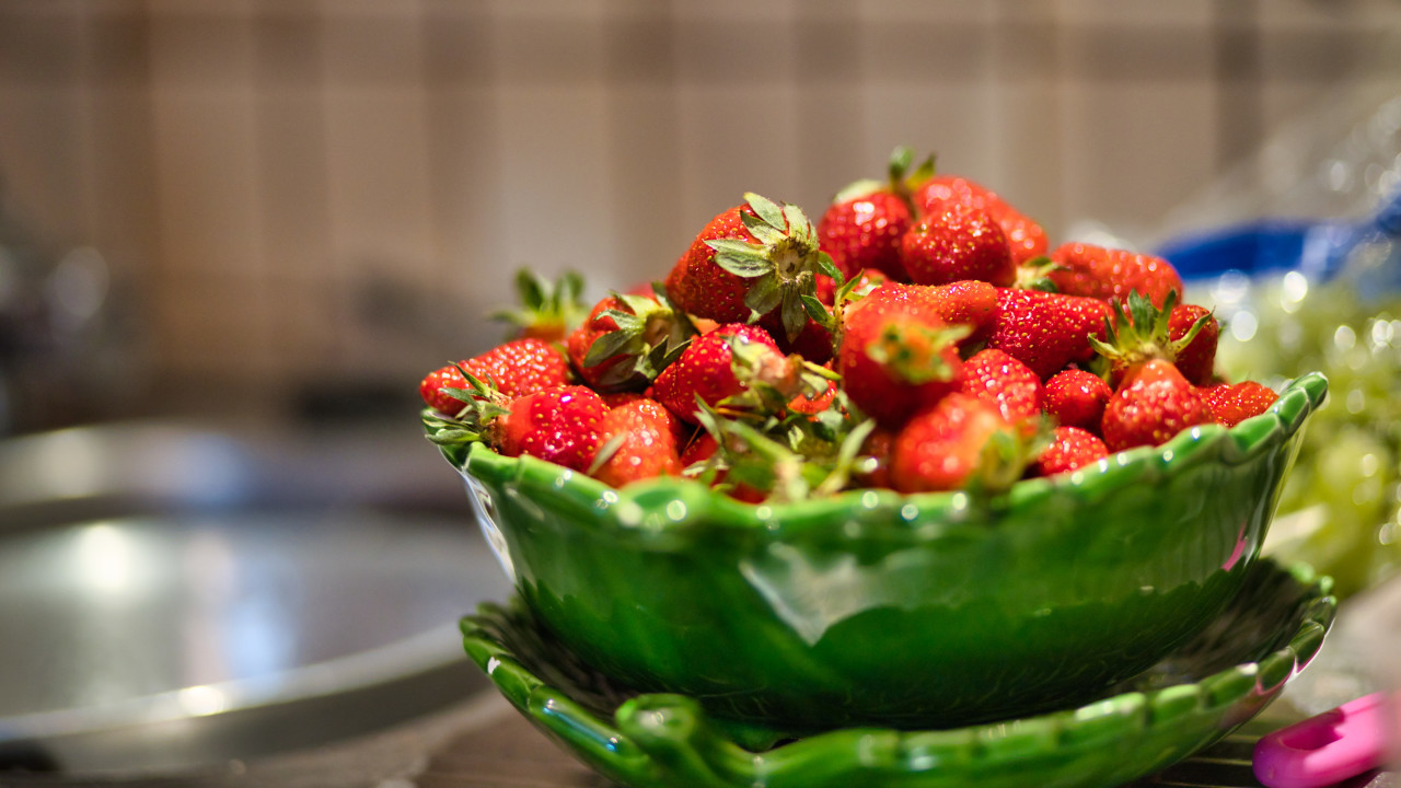 Strawberries in a green bowl in the kitchen