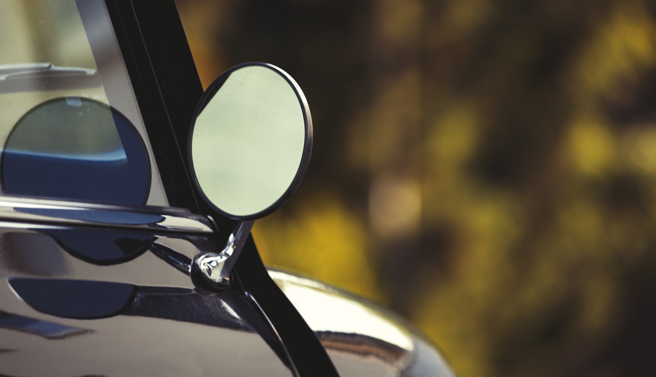 Side rear-view mirror and reflection in the window on black retro car