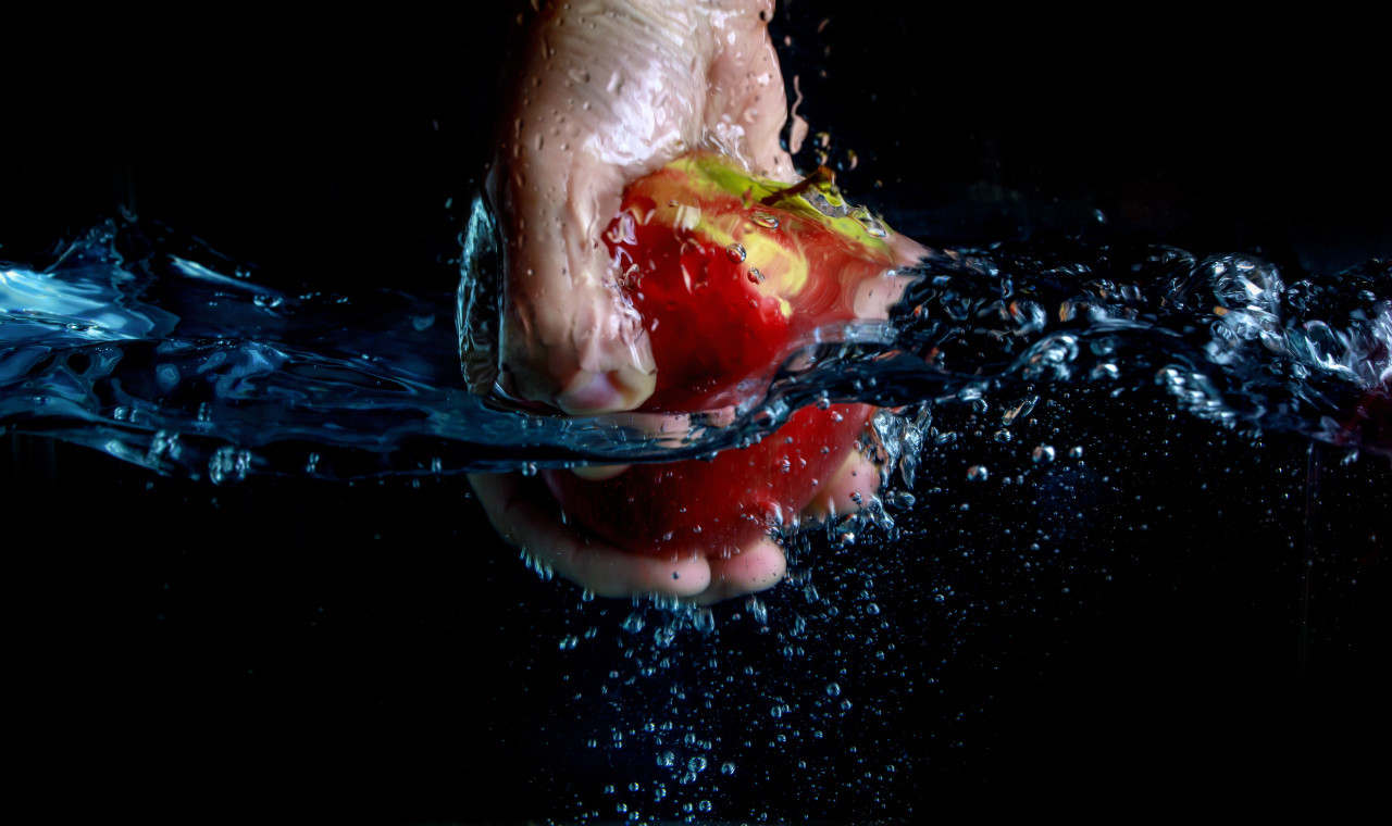 An apple being pulled out of the water by hand isolated on a black background