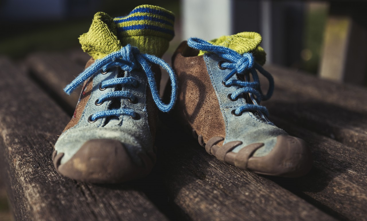childrens shoes on a park bench
