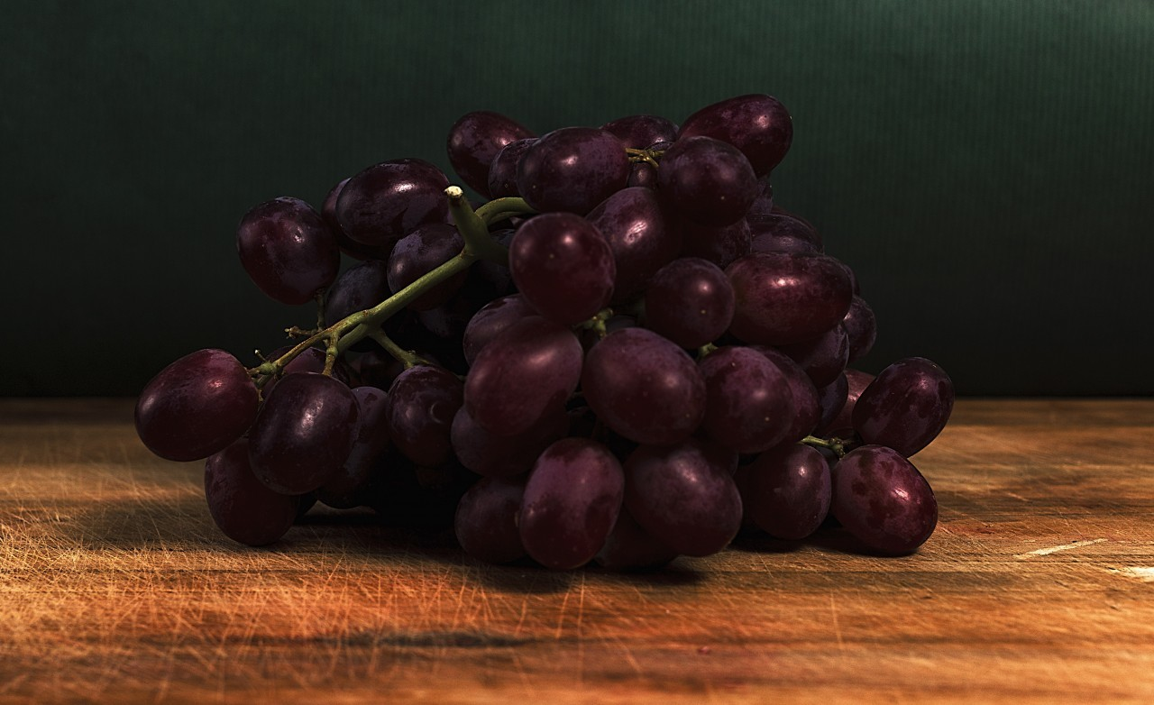 red grapes on a wooden board in a kitchen