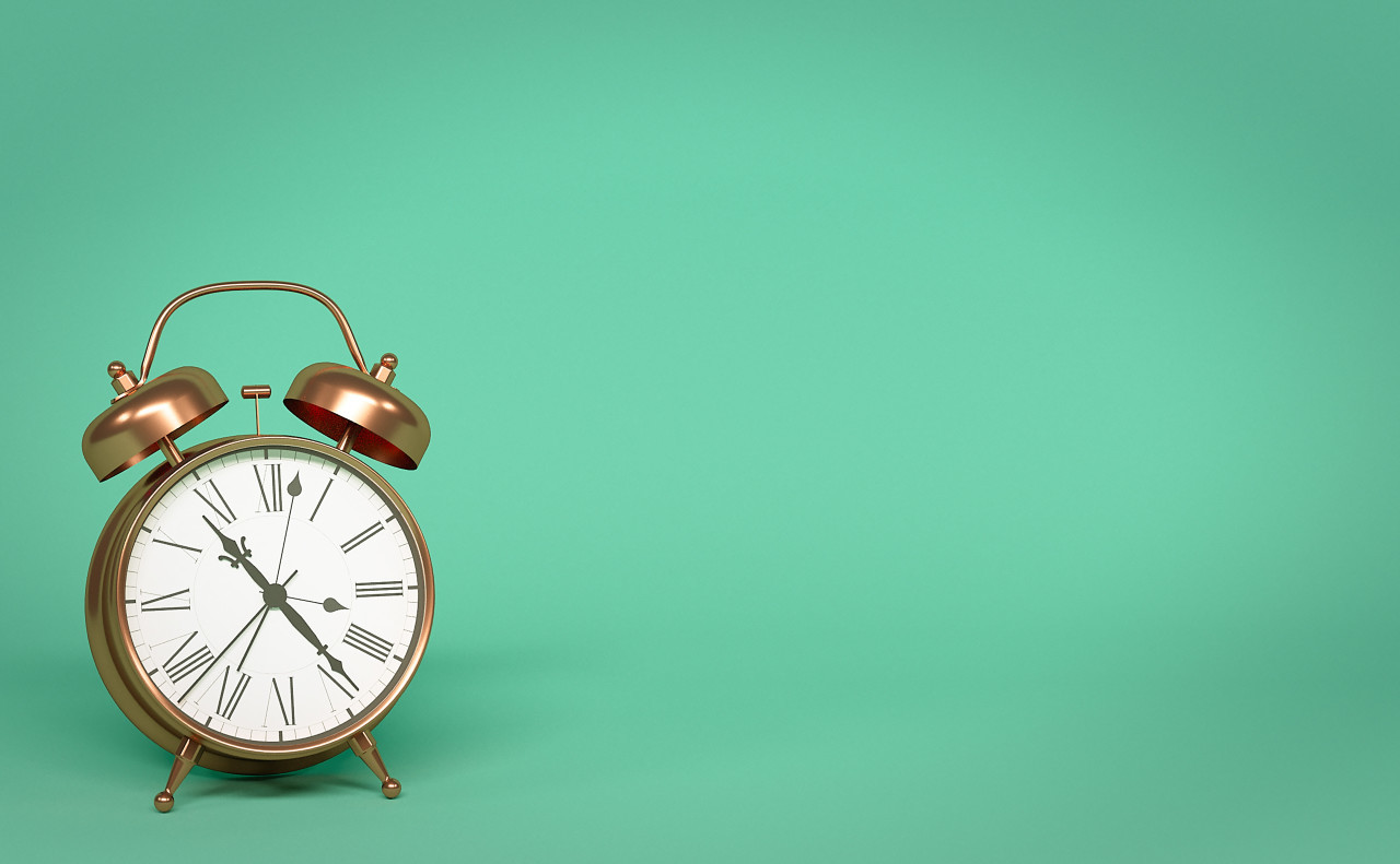 alarm clock isolated on green background