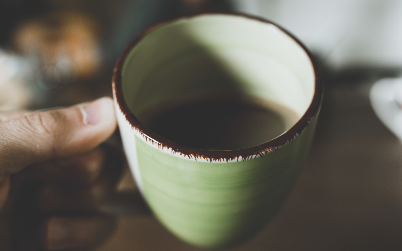 Male hands holding cup of coffee