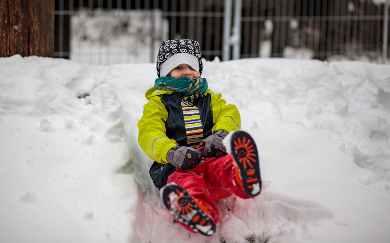 Boy dashes through snow with a sledge