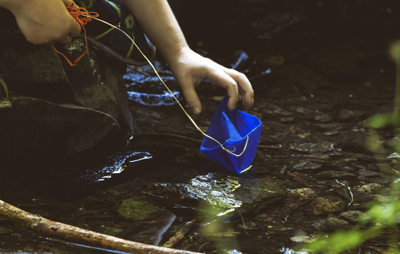Child plays with blue paper boat by a stream