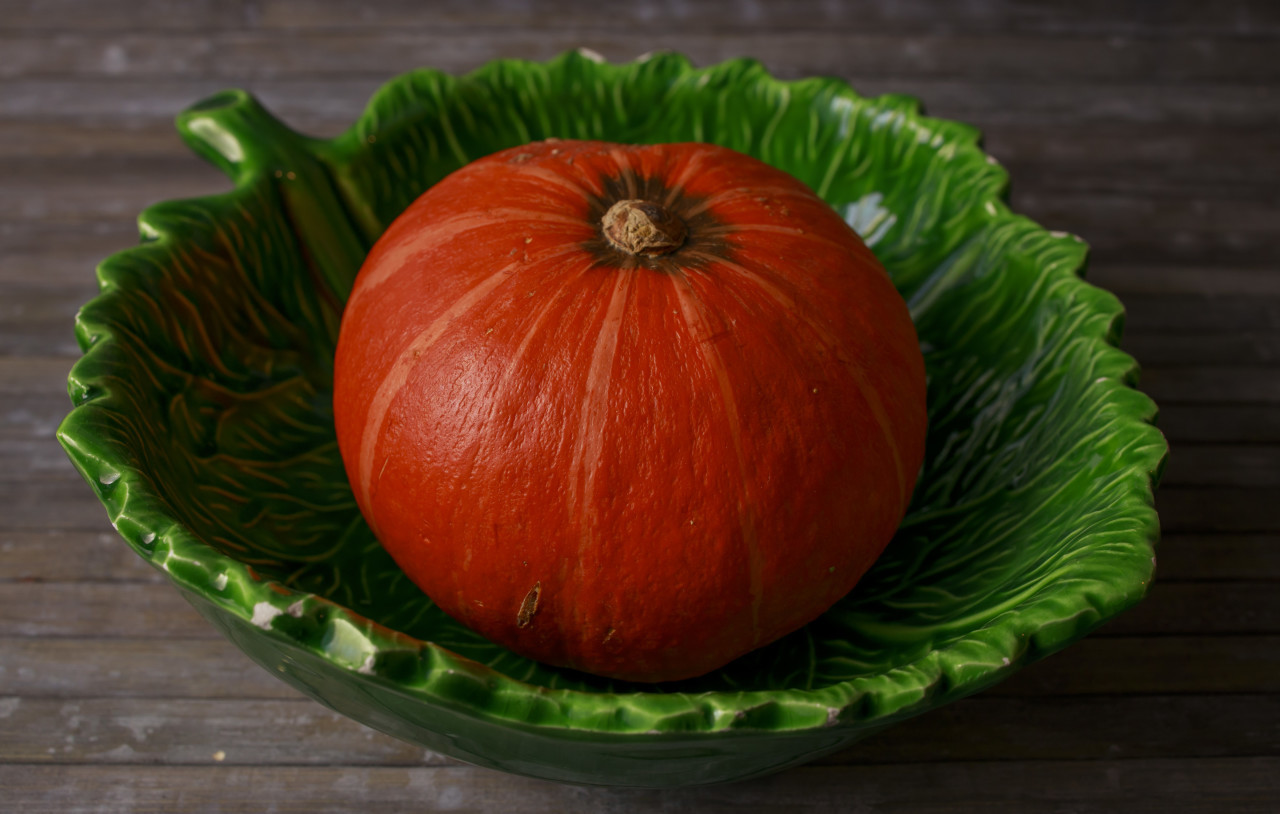 Whole pumpkin in a leaf-shaped bowl