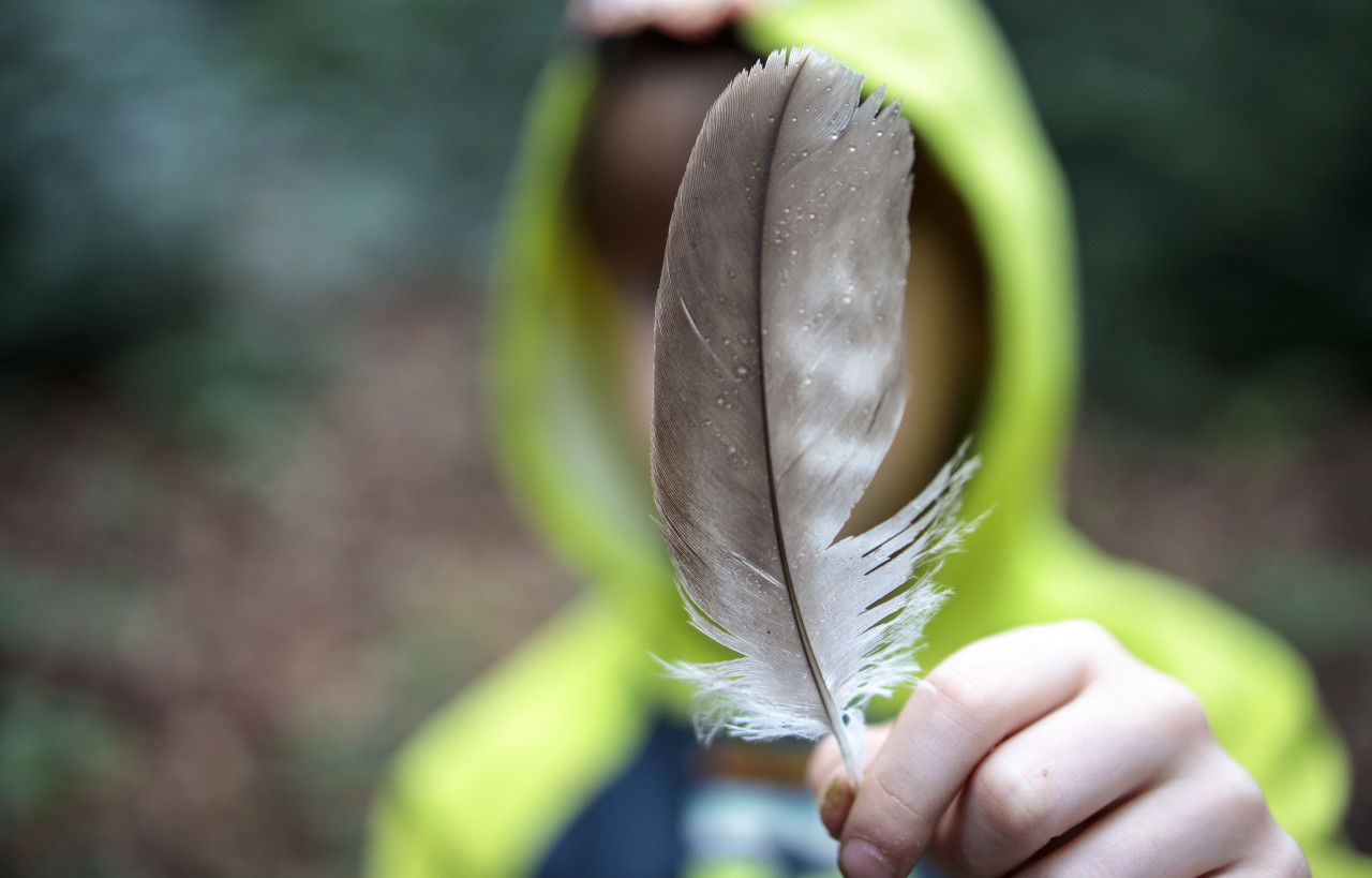 Little boy in rain gear holds a feather at the camera