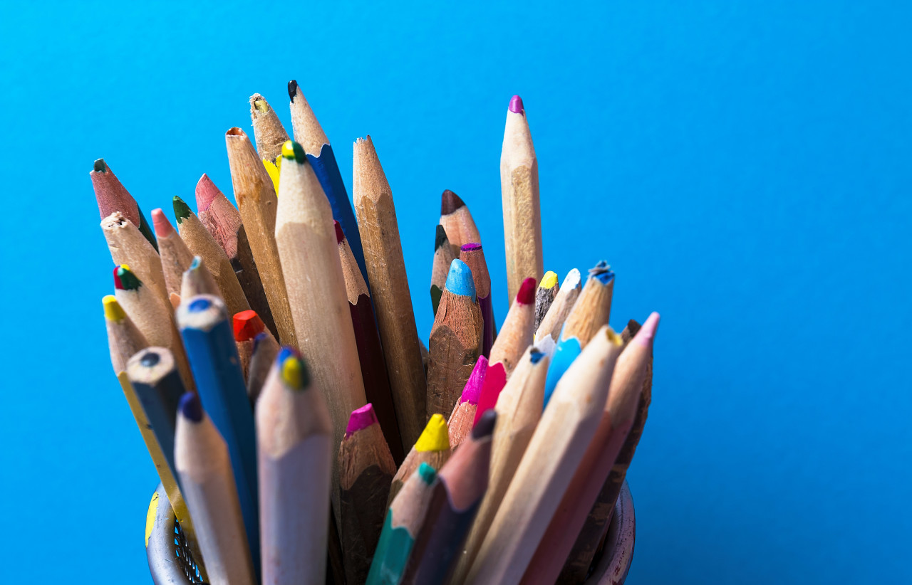 childrens color pencils on blue background