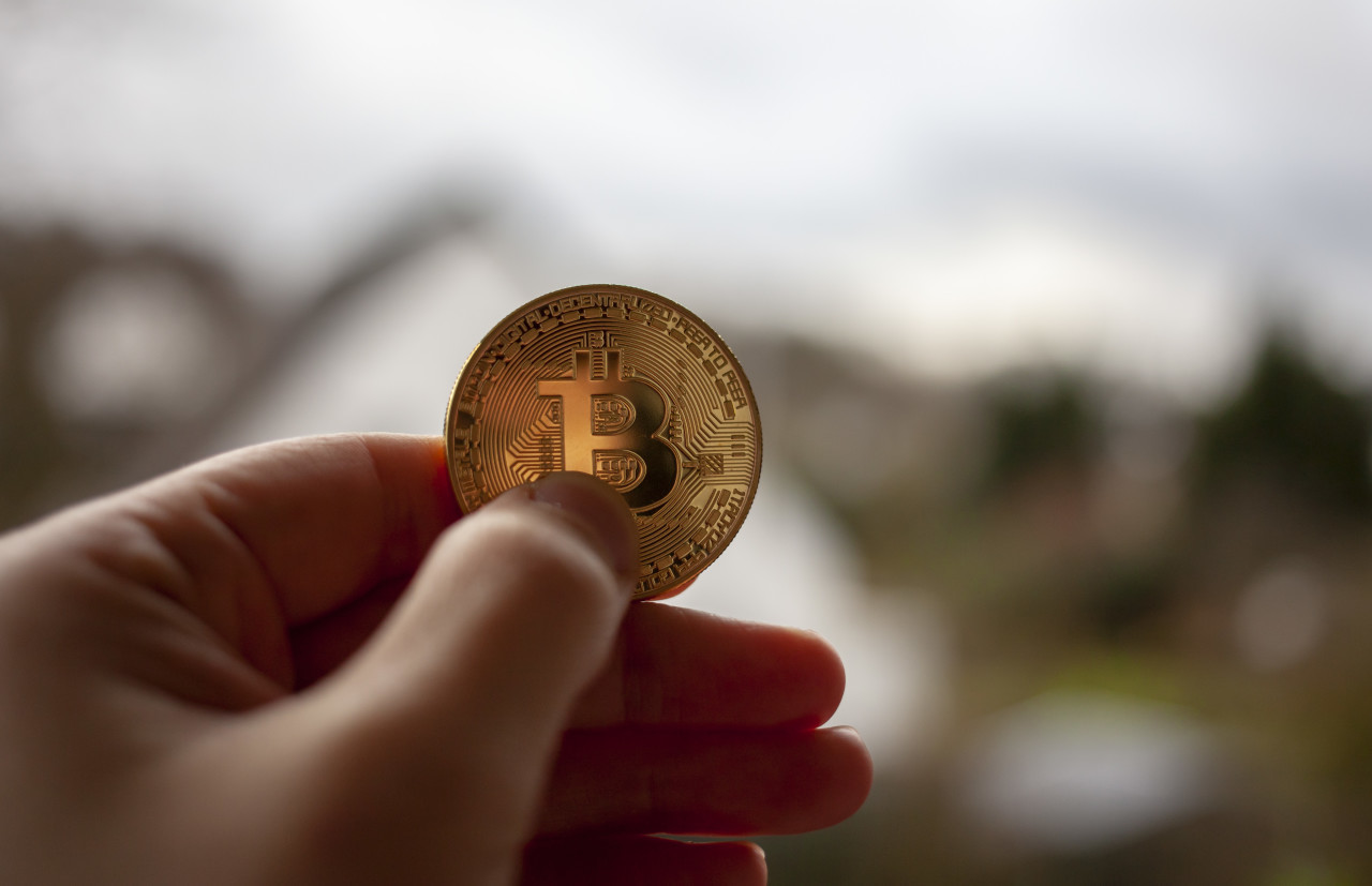 Close up of male hand holding Bitcoin