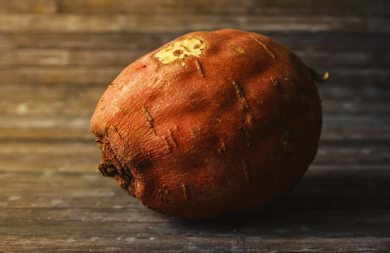 Wrinkled sweet potato on wooden background