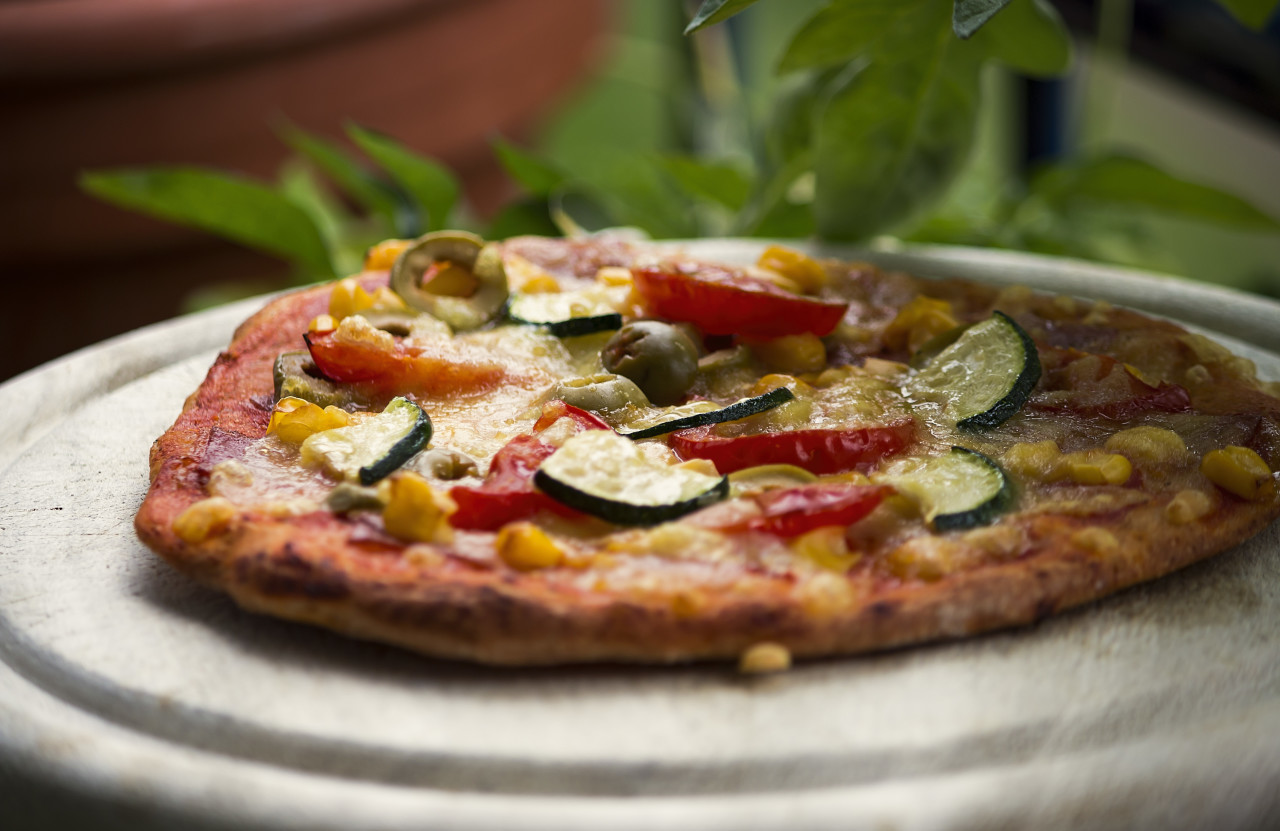 pizza with zucchini spinach olives corn tomatoes on a wooden board