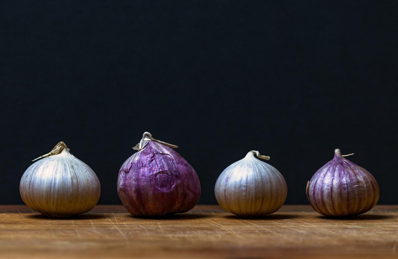 four garlic bulbs on a wooden board - black background