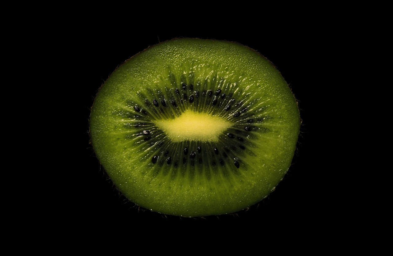 Slice of a kiwi fruit on a black background