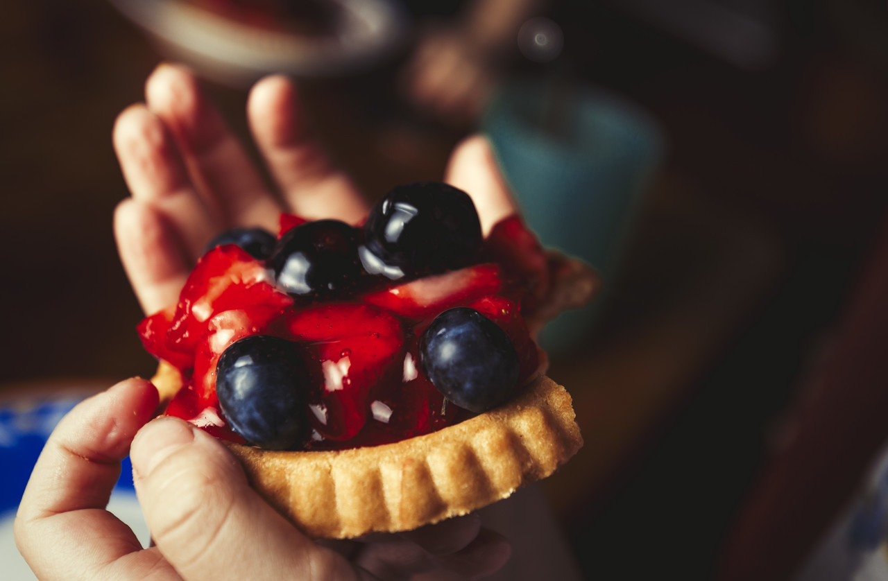 Sweet tart with berries in a hand of children