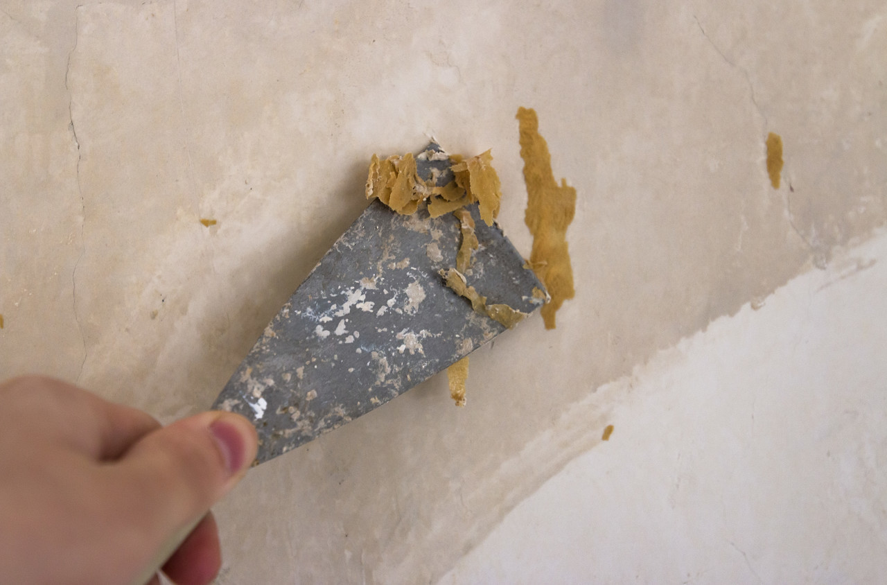 Hands removing old wallpaper with the help of a spatula during the repair in the room.