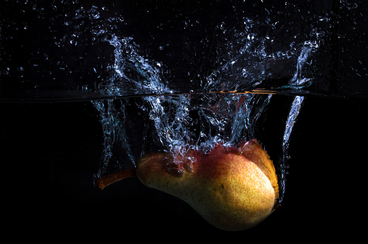 Pear falls into the water with lots of water splashes on a black background