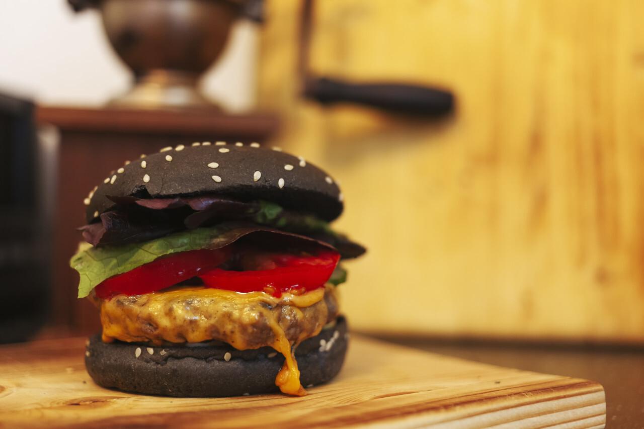 black hamburger on a wooden plate