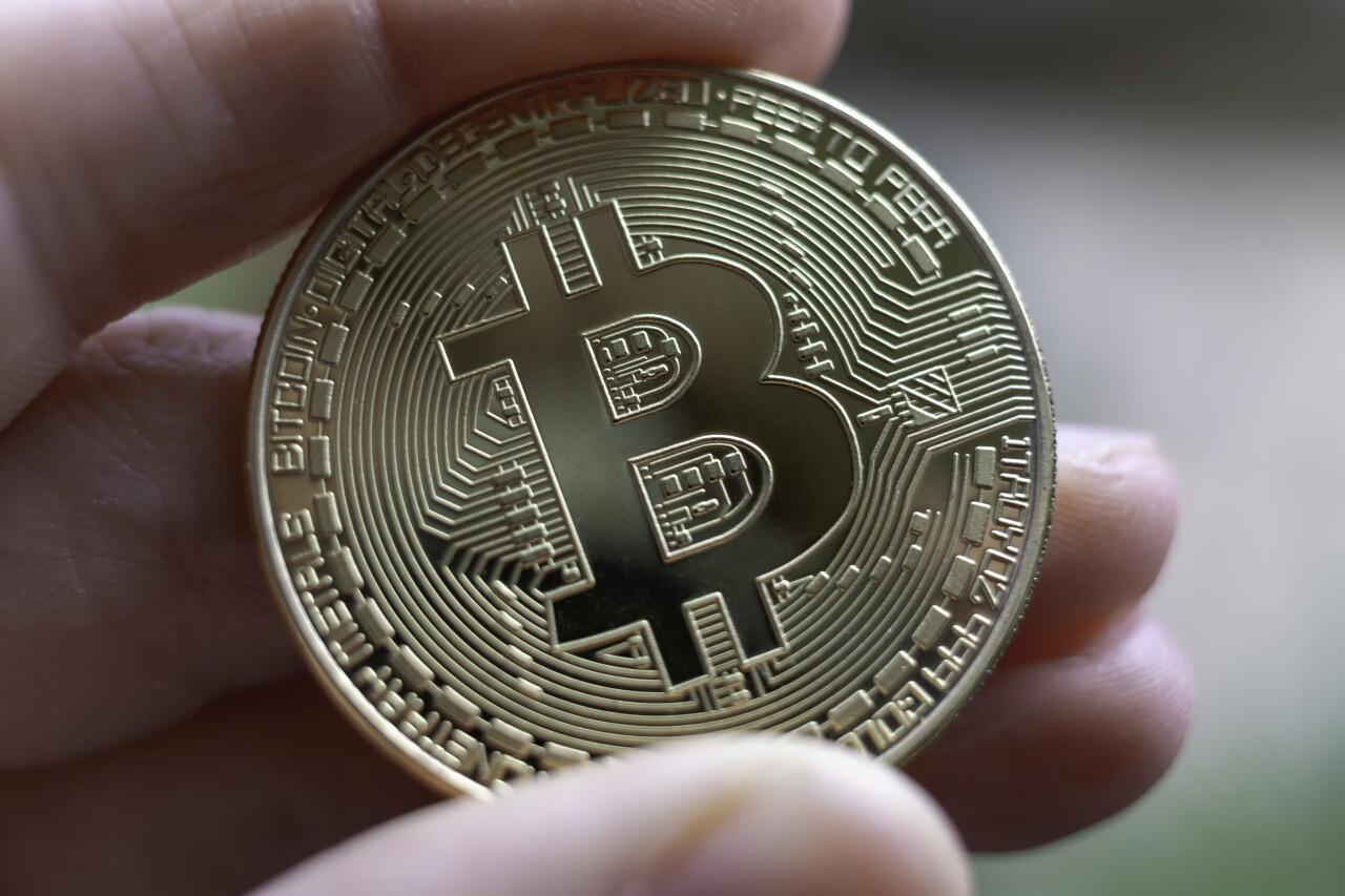 Golden Bitcoin between human fingers