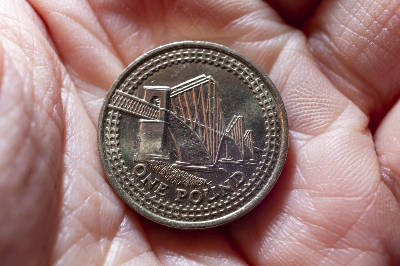 One British pound in a hand, money coin background