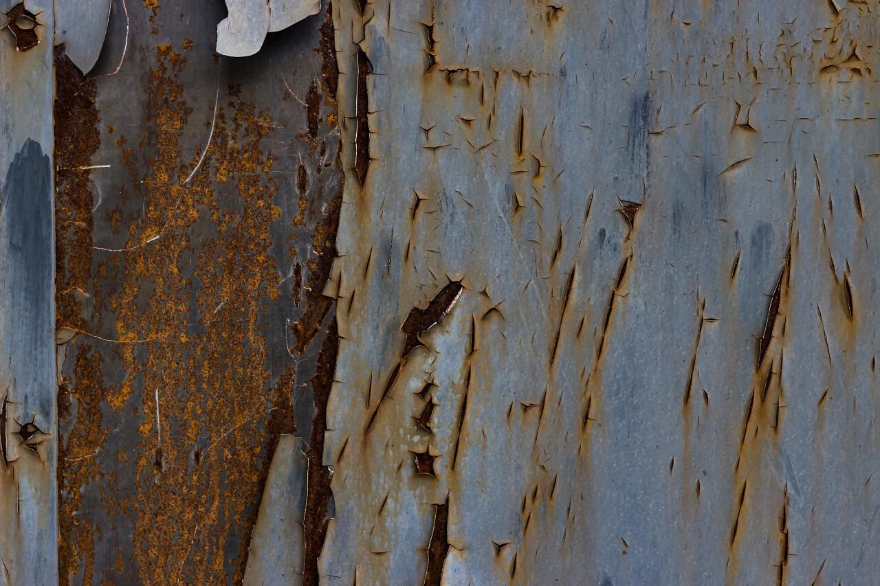 worn steel texture  blue paint rolls off