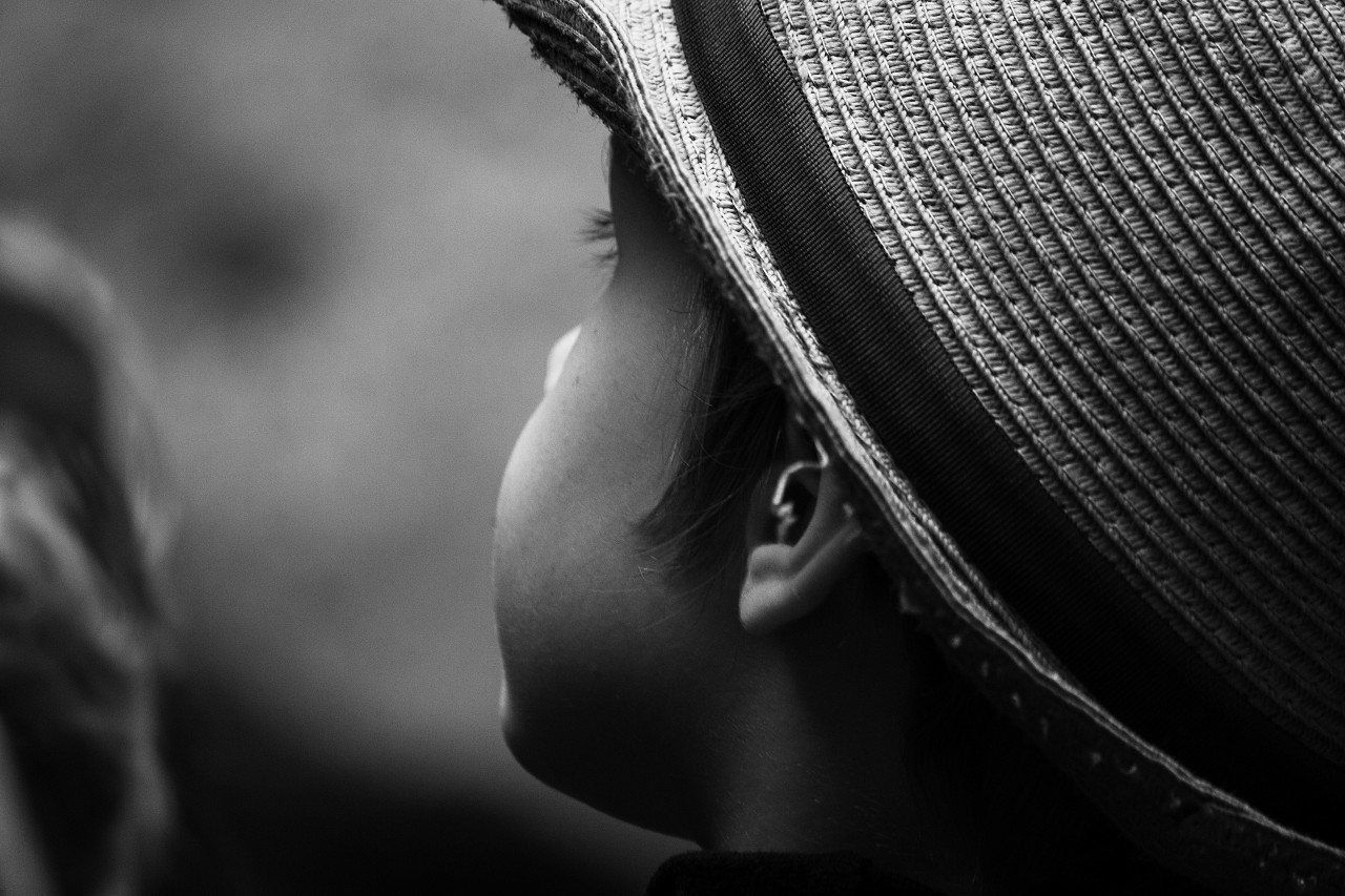 child with straw hat black and white