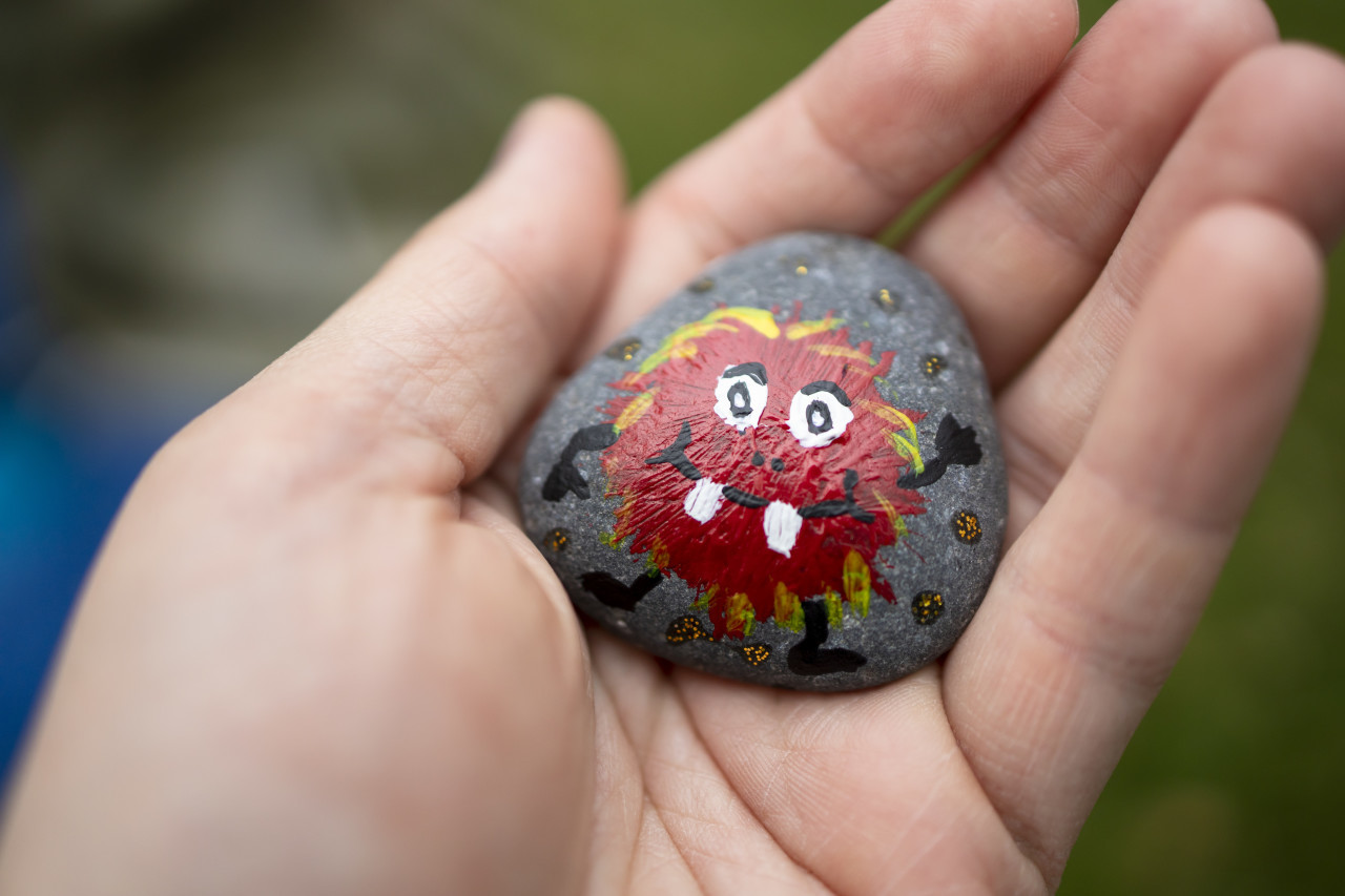 A stone on which a child has painted a red monster in a hand