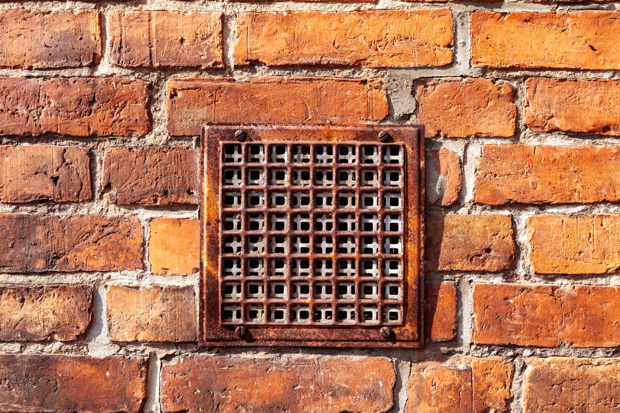 Red brick wall with a built-in ventilation duct texture background