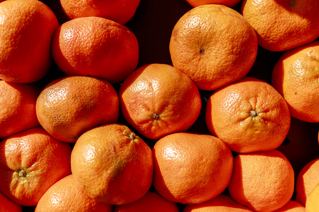 Background of ripe mandarins for sale at the fruit market
