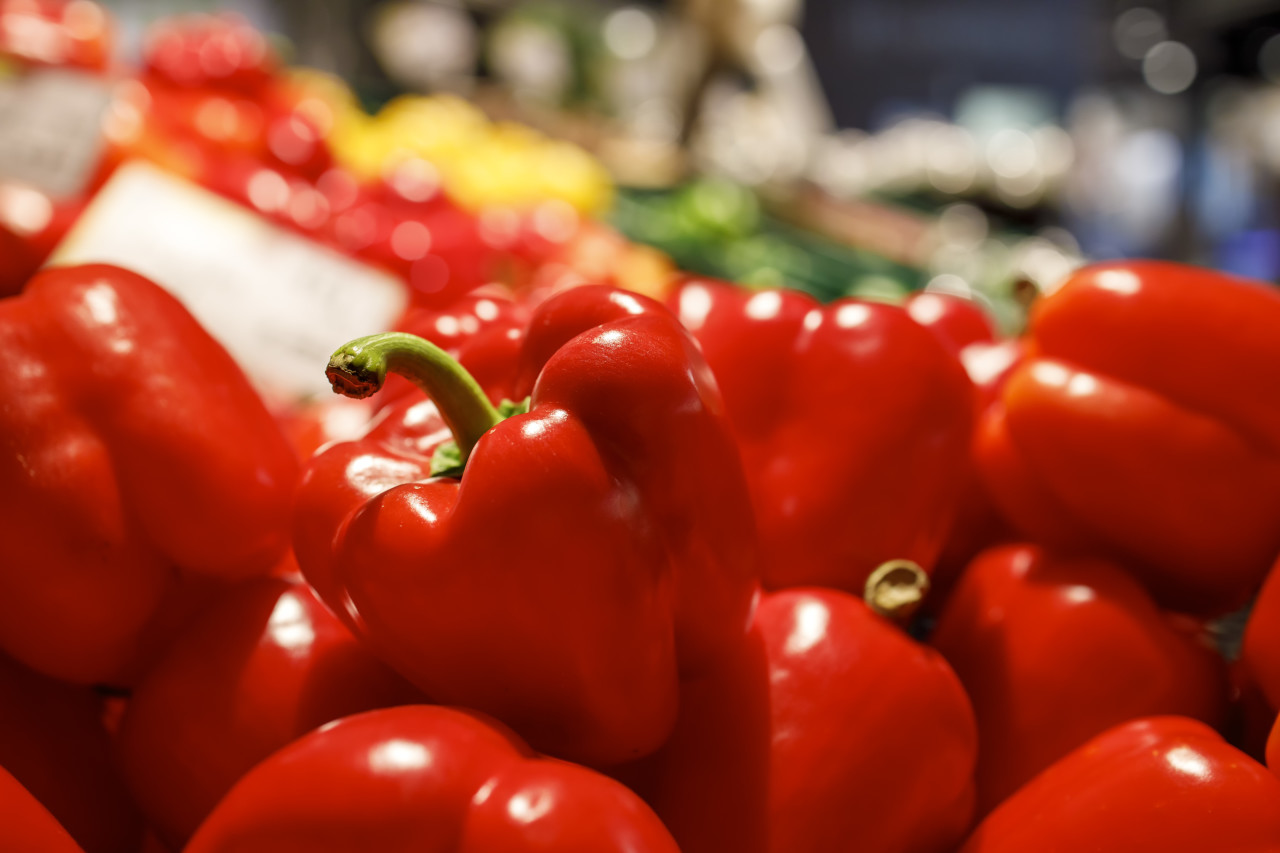 Red peppers are offered for sale in a market