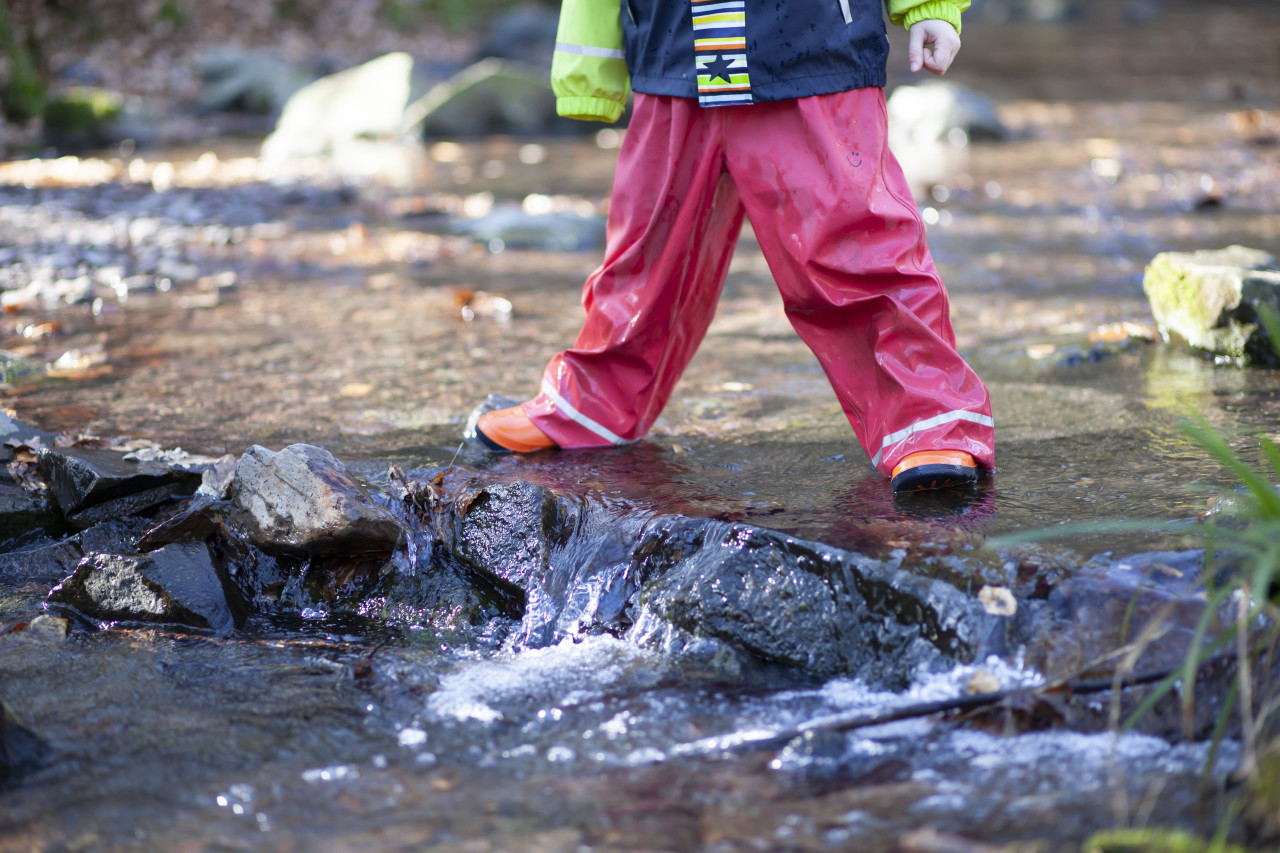 Child with rainwear and rubber boots standing in a stream