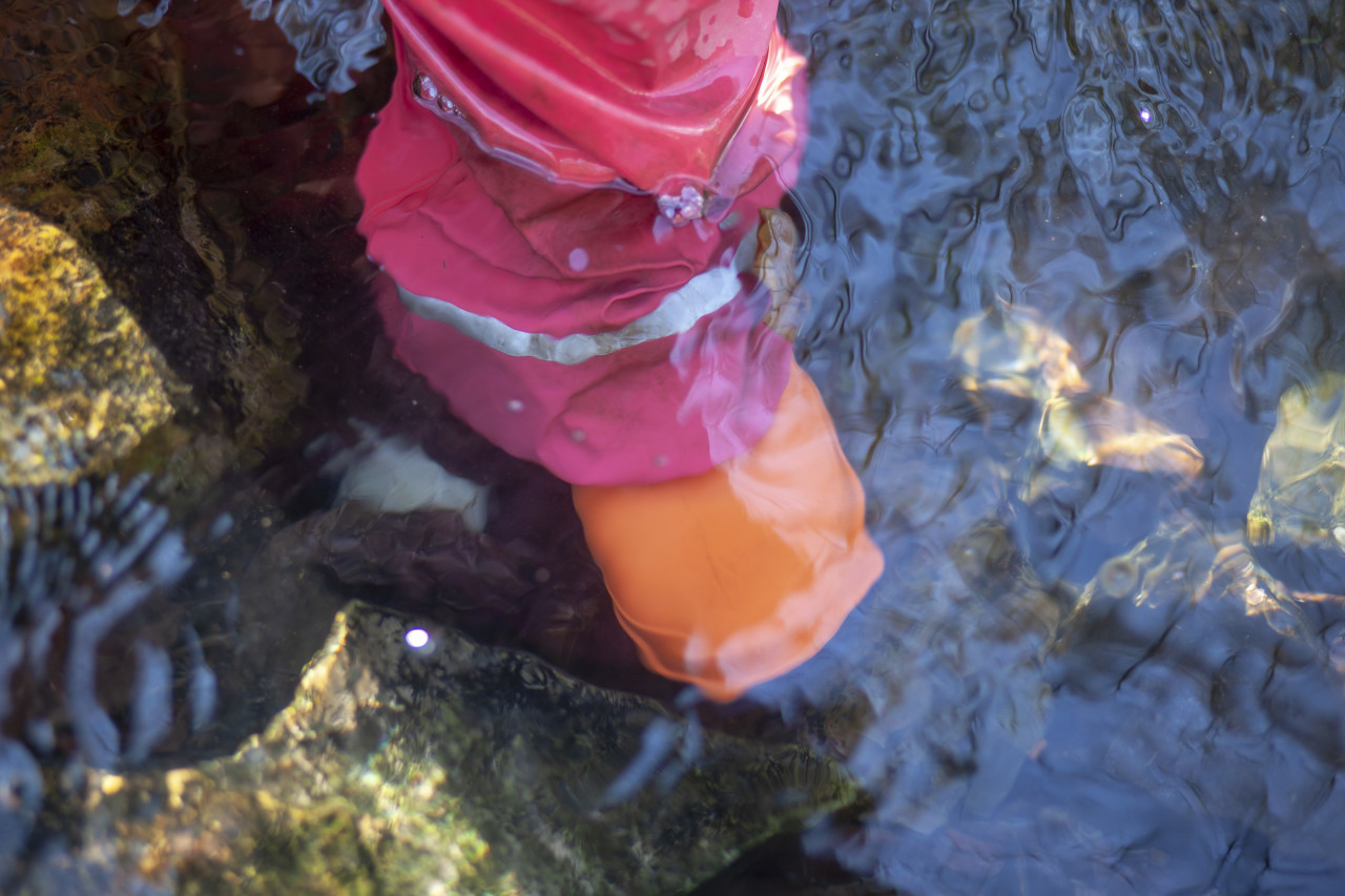 Child with rubber boots standing in a stream