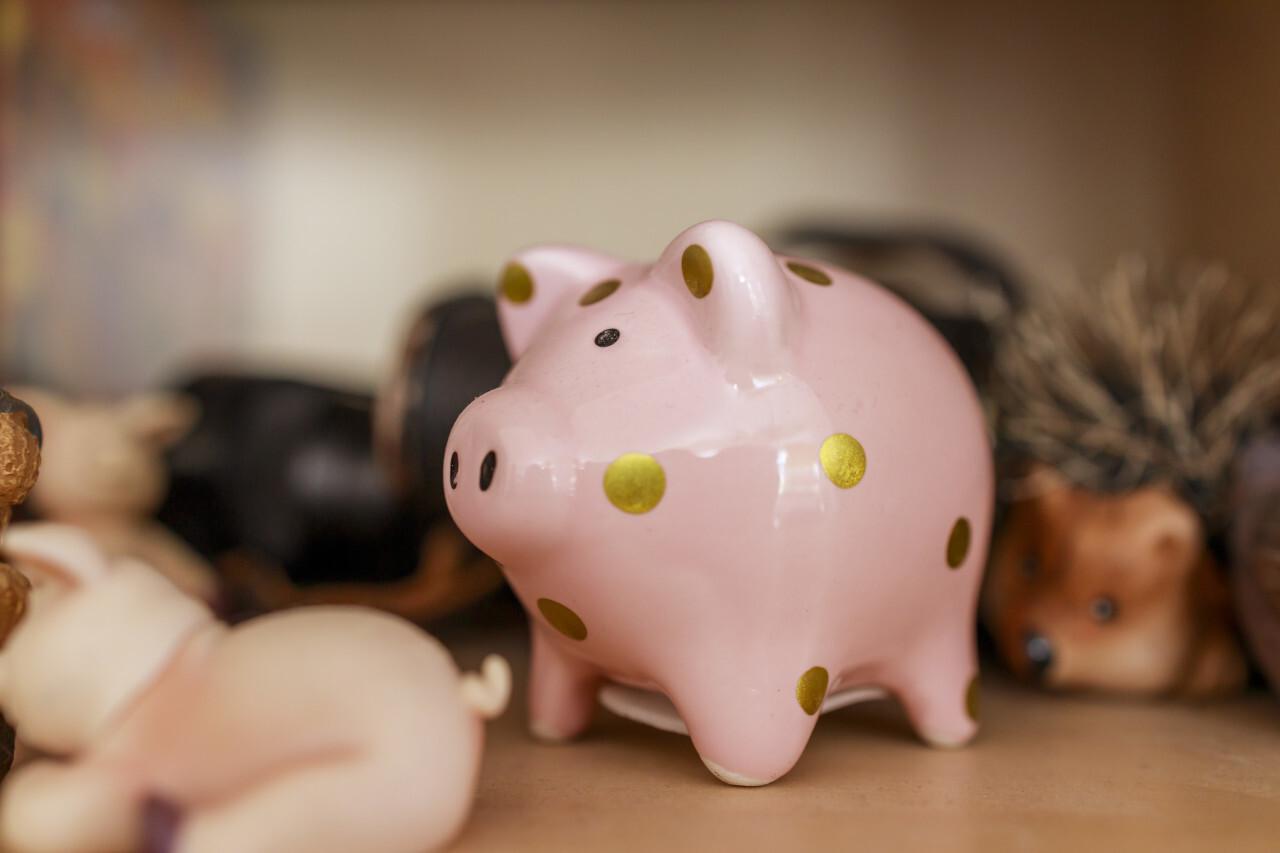 Pink piggy bank with golden dots on a shelf
