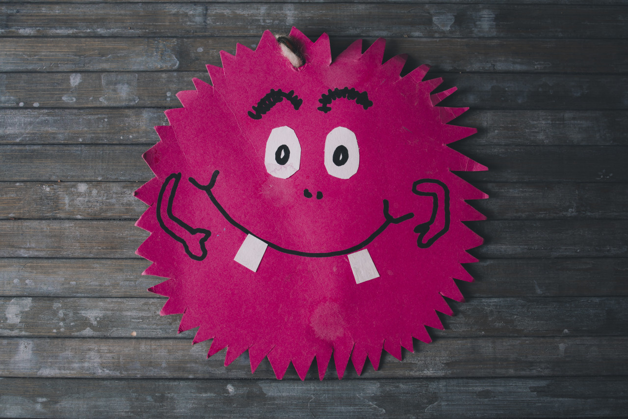 Friendly smiling pink monster on wooden background