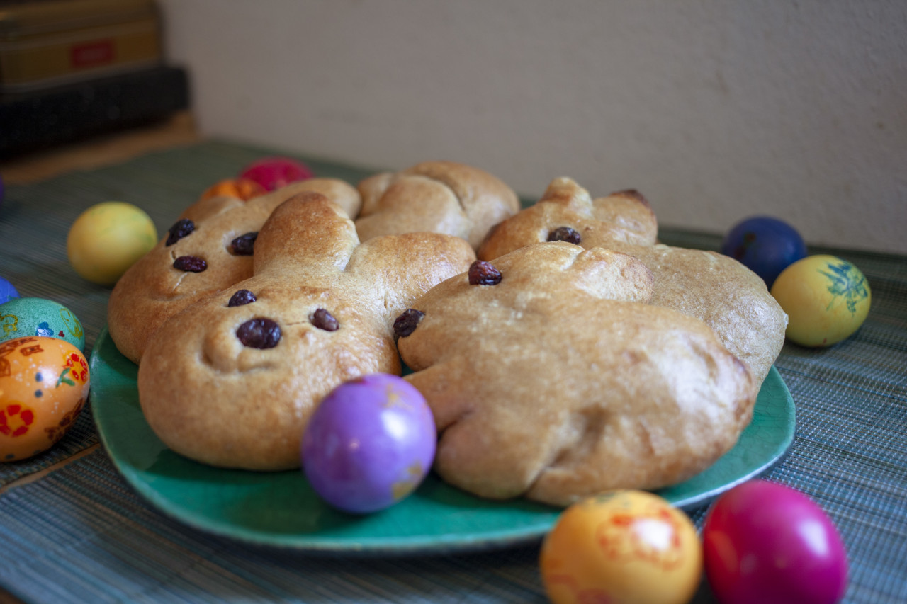 Plate with bread in an Easter bunny shape with easter eggs arround it