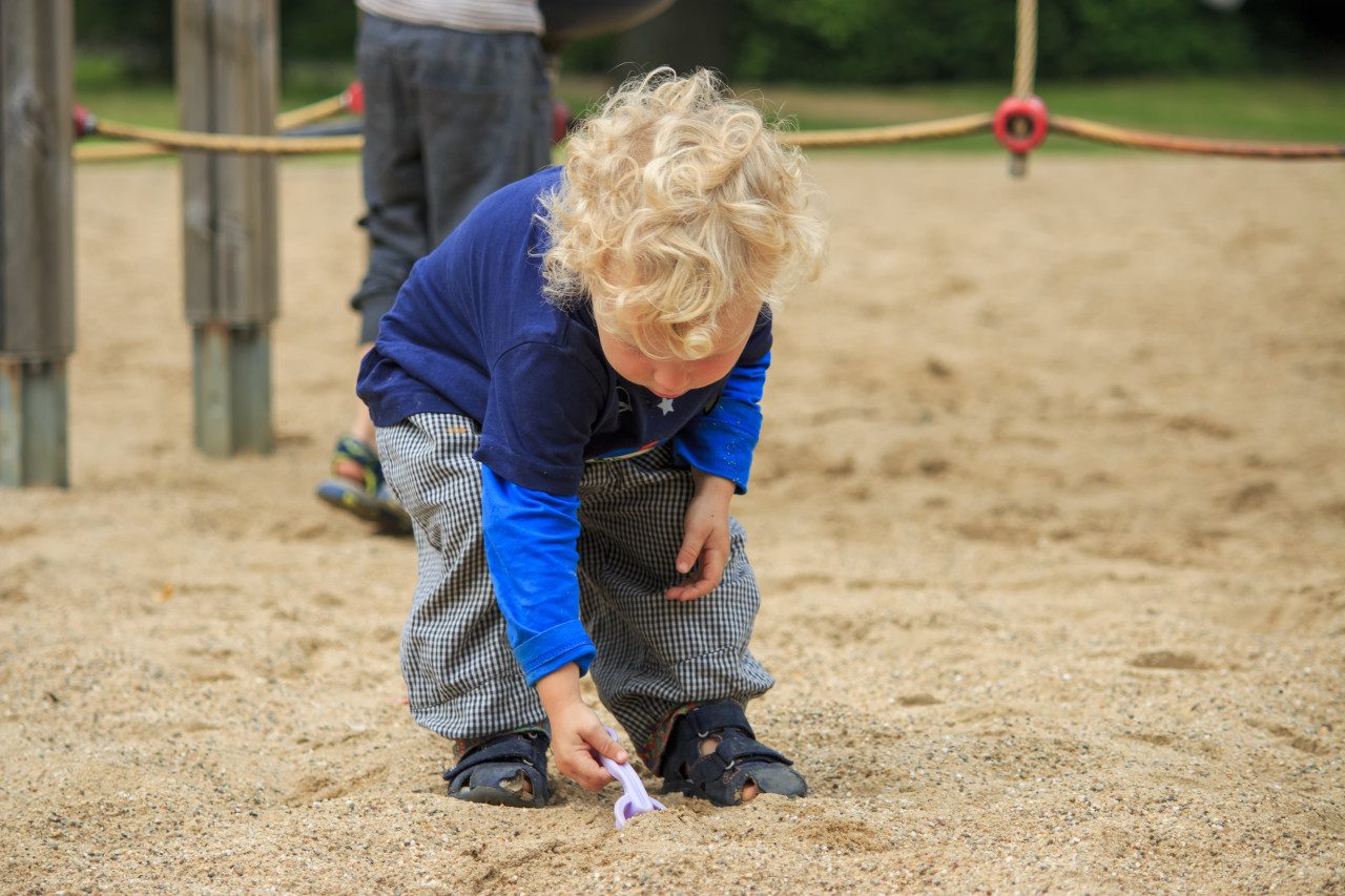 toddler is playing in the sandbox
