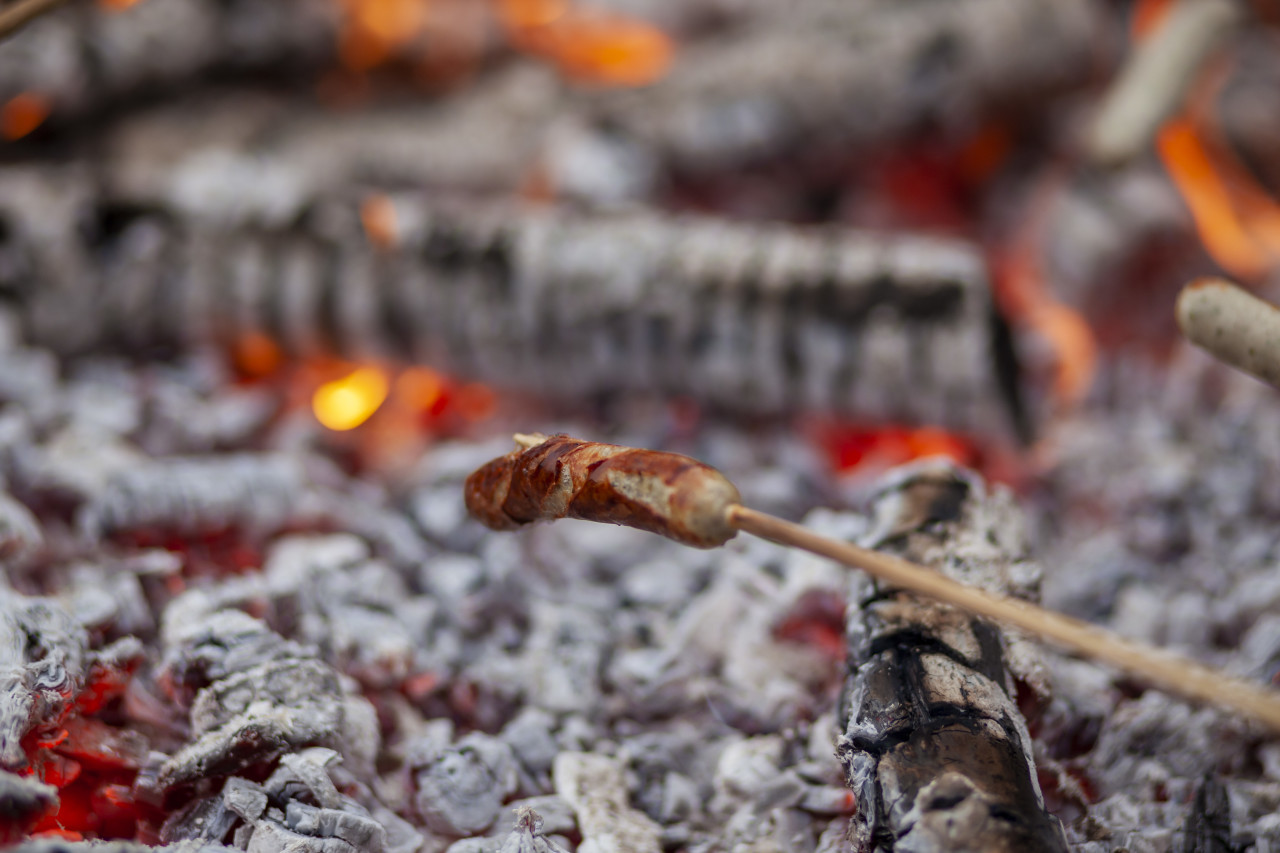 Barbecue sausages on sticks in bonfire