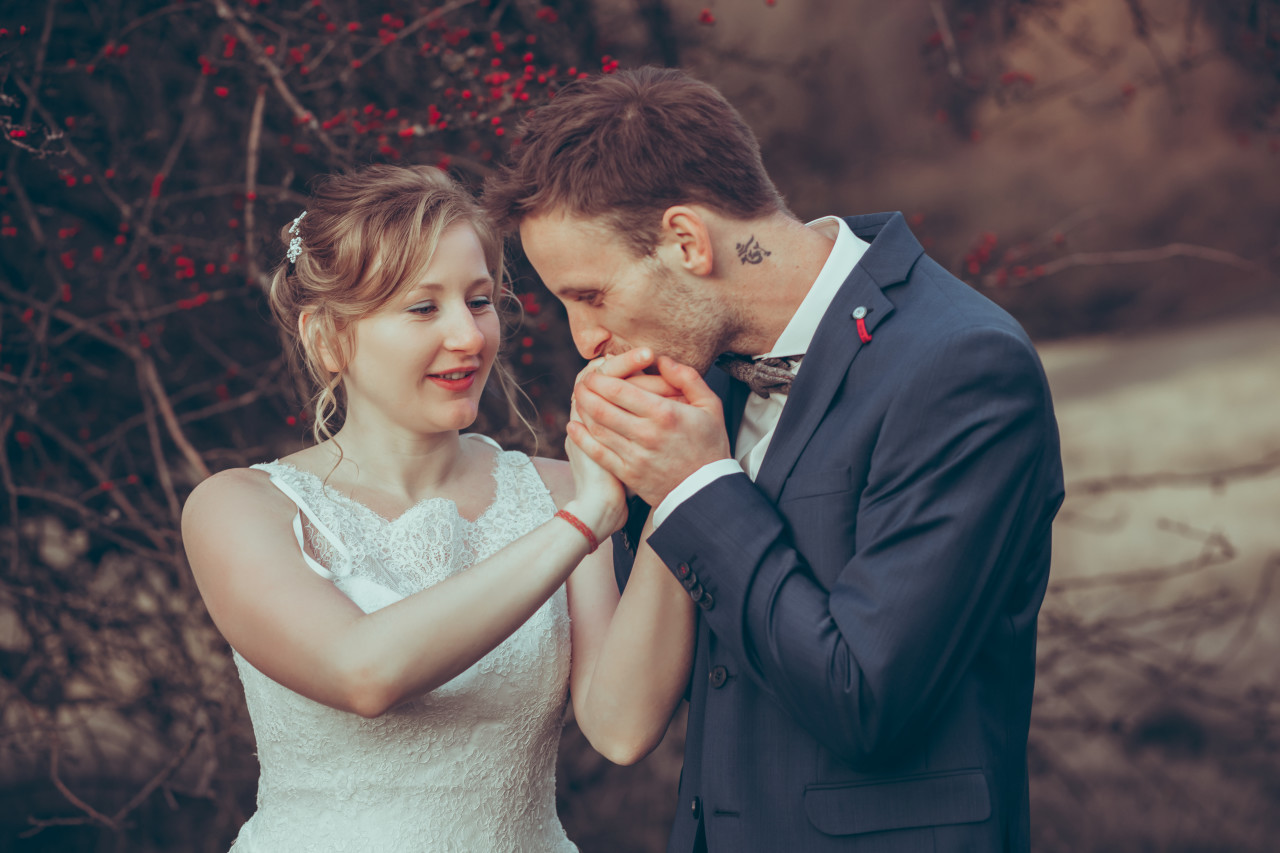 Husband kisses his wife's hand shortly after the wedding