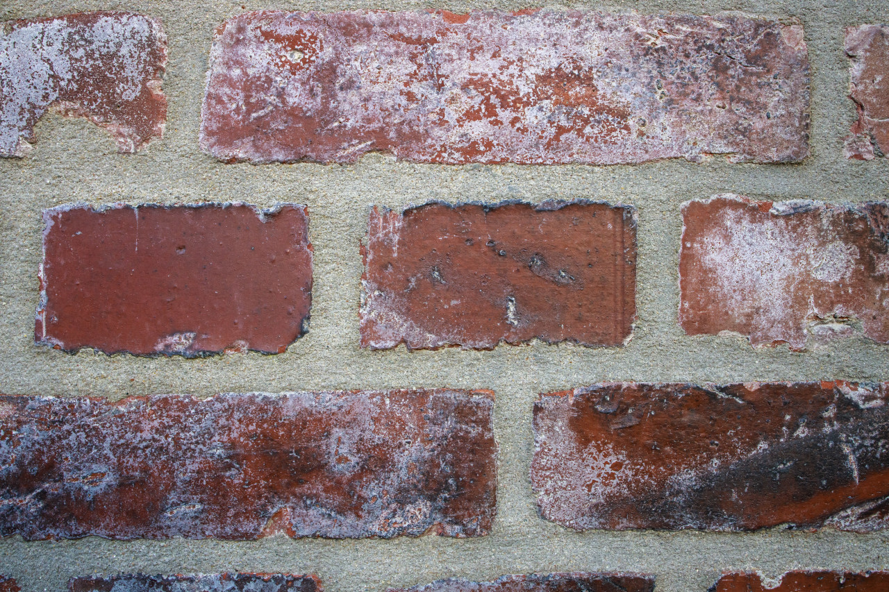Weathered stained old brick wall