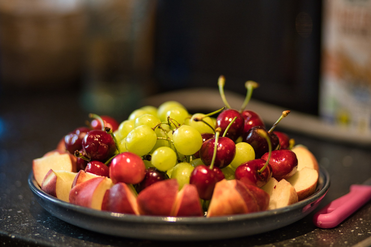 Plate in the kitchen filled with cherries, grapes and pieces of peach