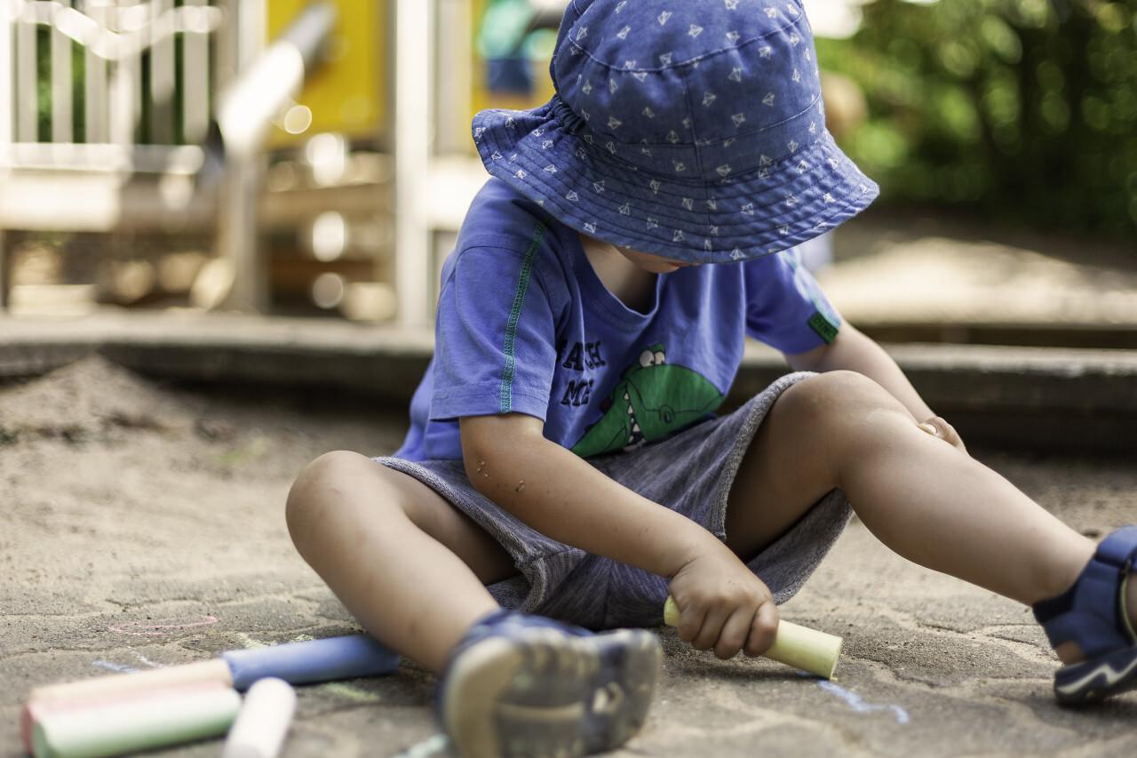 boy paints chalk on the pavement