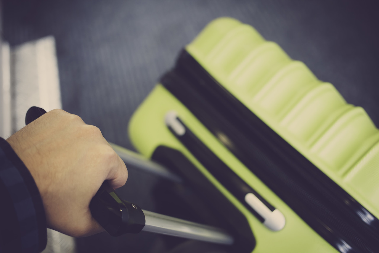 traveler with green suitcase