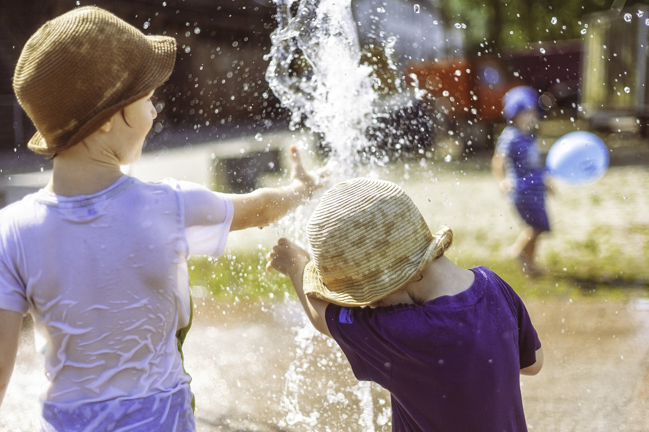 children play at the fountain summertime